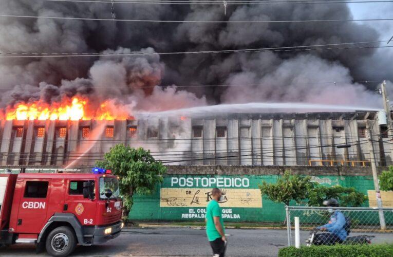 Bomberos intentan sofocar fuego afecta reconocida colchonería en ensanche La Fe